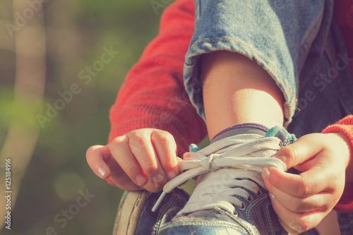 Fotografía  Kid girl tying her shoes.