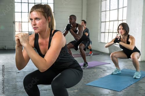 Fotografie, Obraz  Female instructor leads boot camp class in power yoga pose high intensity cardio