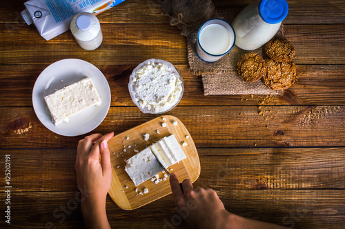 Photo sur Toile Produit laitier Dairy products. Hands cut cheese with a knife. On wooden background.Top view. Flat lay.