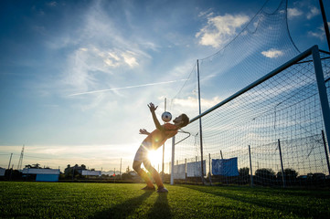 Fototapeta na wymiar Football player is training at the field on a sunset background