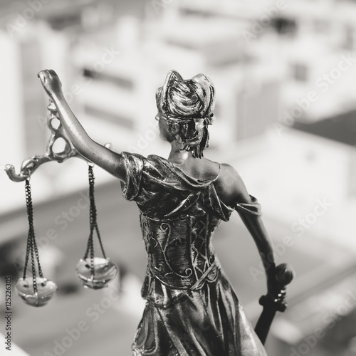 Fototapety, obrazy: Back view of Lady Justice, statuette of the Themis goddess. Law concept. City buildings outdoor background
