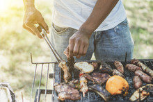 Afro American Man Cooking Meat On Barbecue