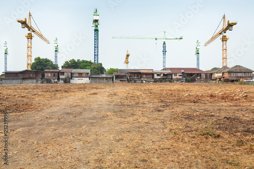 Fotografija  crane construction in front of the village with vacant land
