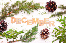 Word  December Against The Background Of Tree Branches, Cones On