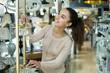 Modern girl selecting chandelier for interior