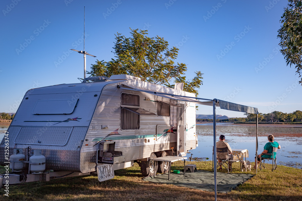 Fototapety, obrazy: Retired couple with small dog sitting enjoying view to lake alongside modern caravan