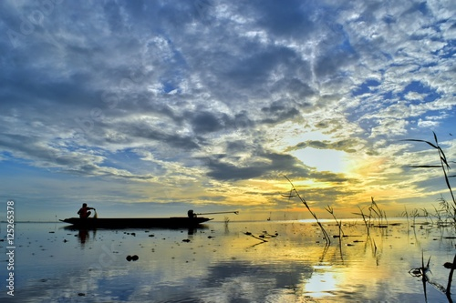 Tuinposter The drift boat on the sea with bluesky and goldsky sunrise backgrund