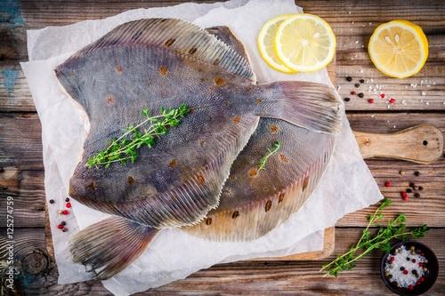 Raw flounder fish, flatfish on wooden table Fototapet
