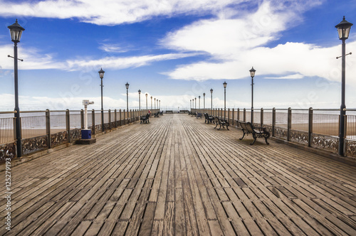 Wooden Skegness pier heading to the sea in the UK. Lamps, perspective, horizon and skies.