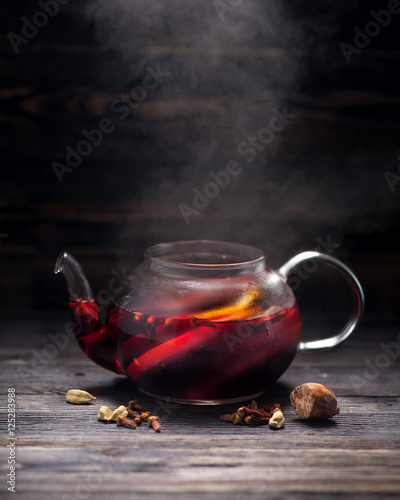 Hot red mulled wine in the glass pot on a dark background