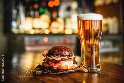 Hamburger and light beer on a pub background. © qwasder1987