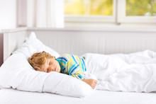 Carefree Little Kid Boy Sleeping In Bed In Colorful Nightwear.