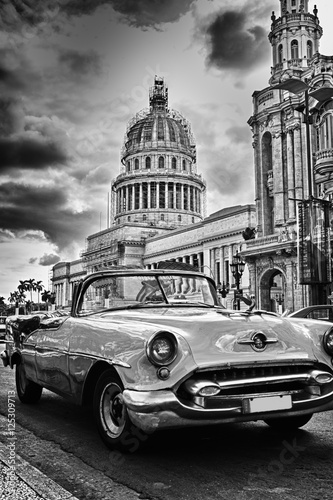 Keuken foto achterwand Vintage cars Black and white image of Havana street with vintage car and Capi