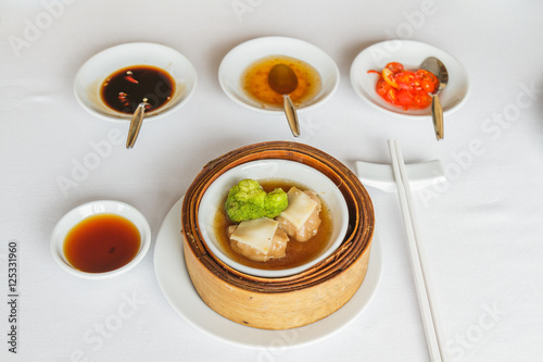 Dim sum food Steamed sliced abalone in brown sauce with broccoli in bamboo basket at restaurant with soy sauce, sweet sauce, chili sauce and chopsticks Canvas Print