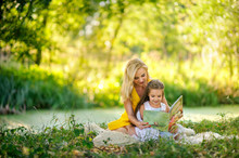 Mother Reads The Book In The Daughter On A Grass