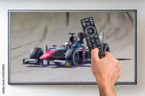 Man is watching formula one racing on TV