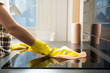 canvas print picture - Housewife in rubber protective cleaning and polish electric cooker. Black shiny surface of kitchen top, hands, detergent.