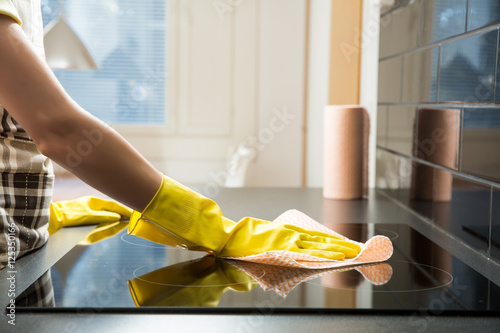 Housewife in rubber protective cleaning and polish electric cooker Canvas