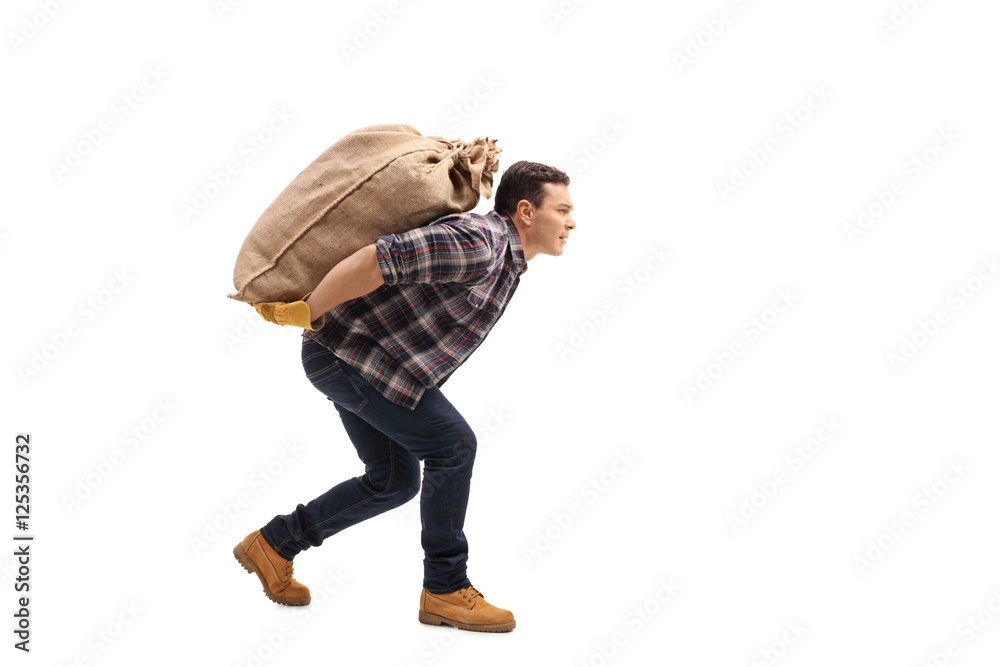 Fototapety, obrazy: Male agricultural worker carrying burlap sack on his back