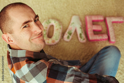 Fotografie, Obraz  Funny adult man smiles while sitting over his name made of pillo