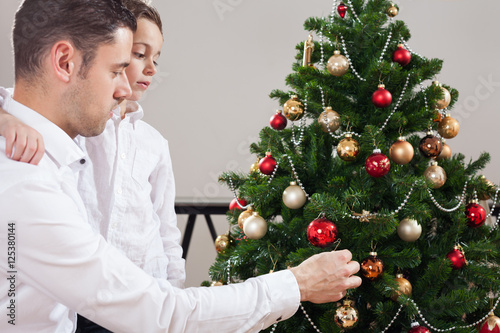 Fotografie, Obraz  father decorating christmas tree with son