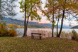 Lonely bench at bank of lake at autumn evening. Sunset in mountain Alps at fall. Foliage in park, Austria Europe Lake Millstatt