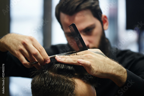 Stampa su Tela The Barber a man with a beard in the process of cutting the client a pair of sci