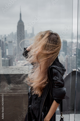 Fotografie, Obraz  Girl on a windy day watching manhattan from Top of the Rock