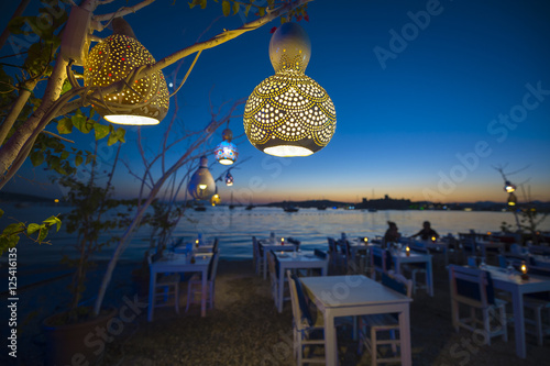 Informal beachside seating with decorative gourd lights hanging from a tree in B Canvas Print