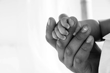 Dad Is Holding Baby Hand. Black And White Photo