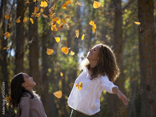 Pinturas sobre lienzo  Madre e hija jugando con hojas de otoño
