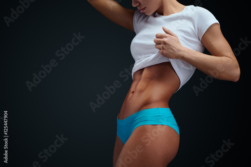 Athletic woman with sixpack abs posing Wallpaper Mural