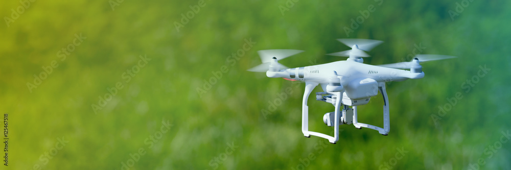 Fototapeta Quadcopter drone flying over a cultivated field
