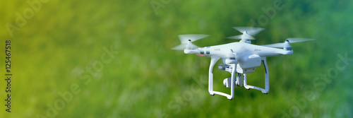 Fototapeta Quadcopter drone flying over a cultivated field obraz