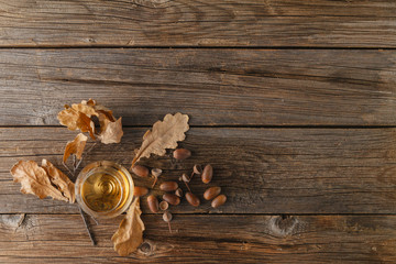 snifter of brandy and dried oak leaves`