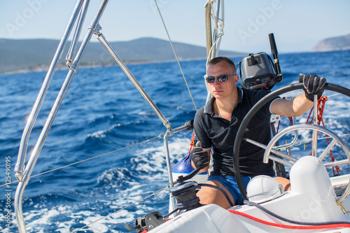 Tuinposter Zeilen Young man steers a sailing yacht boat in the open sea.