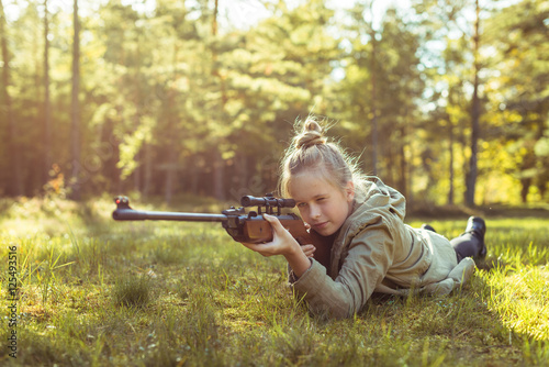 Fotografía  Girl shooting from the air rifle in the forest
