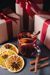 Mulled wine with spices and Christmas present on gray concrete background. Christmas concept. Christmas holiday.