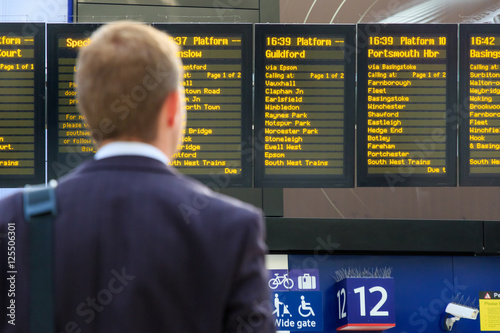 Foto op Plexiglas Treinstation Commuter checking digital timetables at a train station