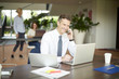 Financial professional man making call and using laptop