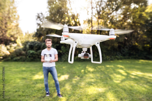 Young hipster man with flying drone. Sunny green nature. Poster