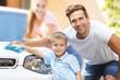 Happy family washing car on street