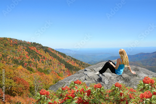 Photo  Young woman siting and relaxing on the top of the mountain