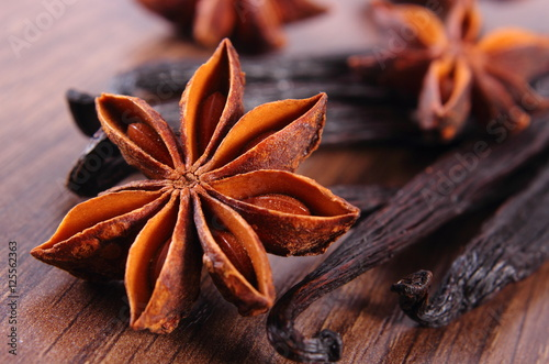 Closeup of star anise and fragrant vanilla on wooden surface plank Wallpaper Mural