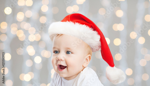 02c804bda71e1 baby boy in christmas santa hat over blue lights - Buy this stock ...
