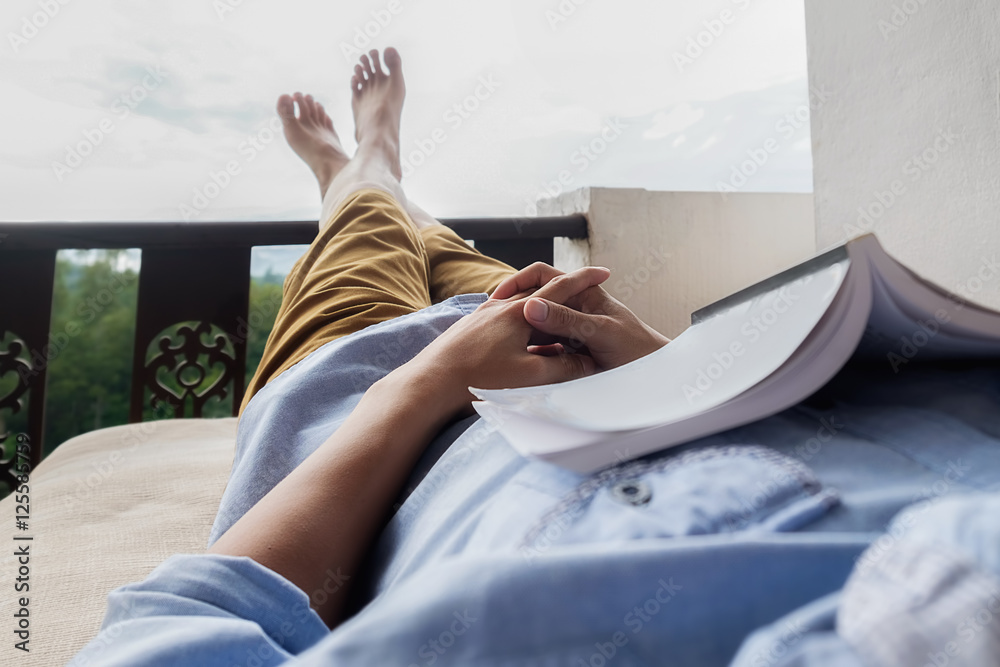 Fototapeta Young man reading a book lying on soft mattress in relaxing bed at terrace with green nature view. Fresh air in the morning of weekend or free day. Relax or education background idea. Selective focus.
