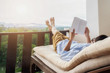 Rear view of asian man relaxing on a sofa and holding book on bed at home terrace with beautiful green background view. Relaxing concept.