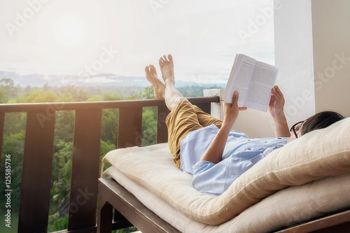 Garden Poster Relaxation Rear view of asian man relaxing on a sofa and holding book on bed at home terrace with beautiful green background view. Relaxing concept.