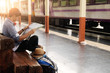 Backpack and hat at the train station with a traveler. Travel concept...