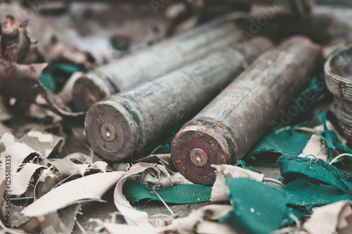 Fotografía  bullet shells from heavy machine gun on the table with camouflage netting